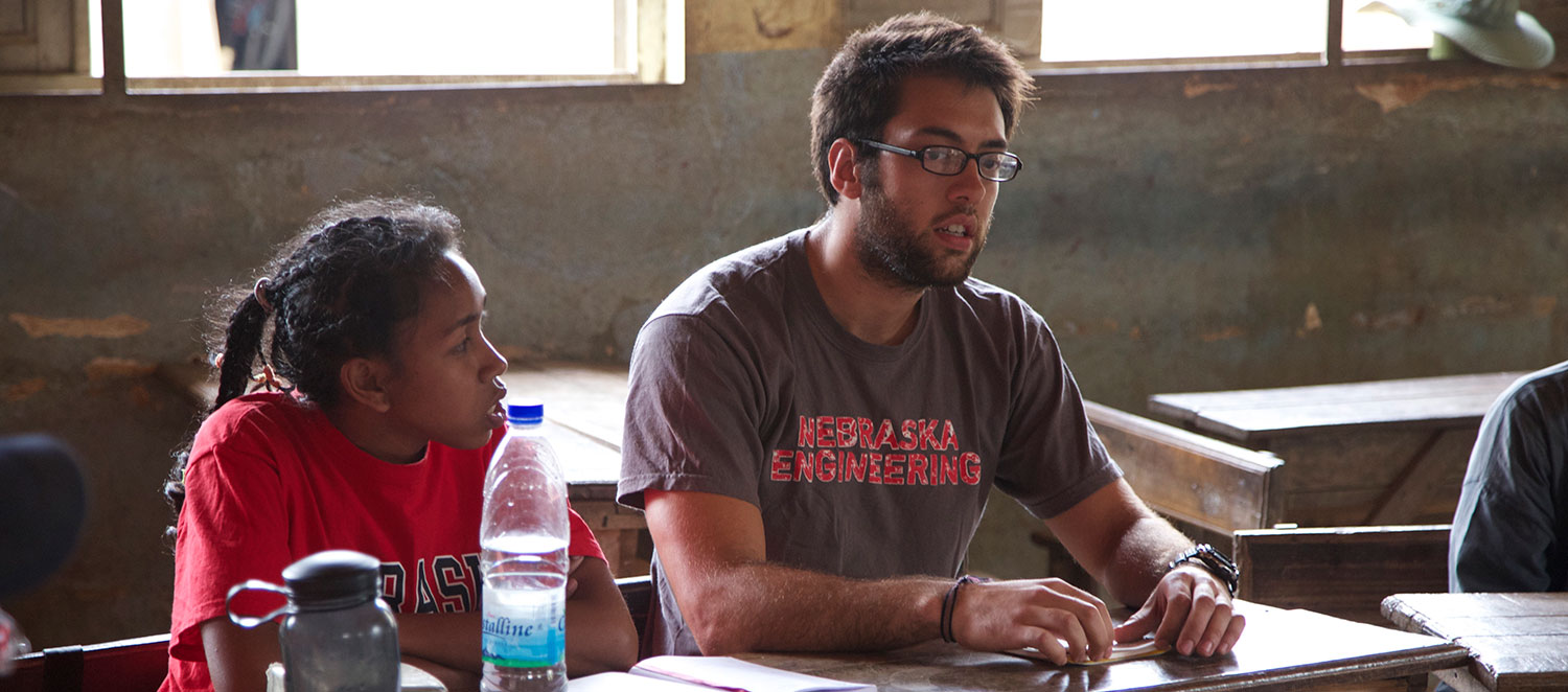 Nebraska Engineering Student sitting with in a classroom with a student during a mission trip