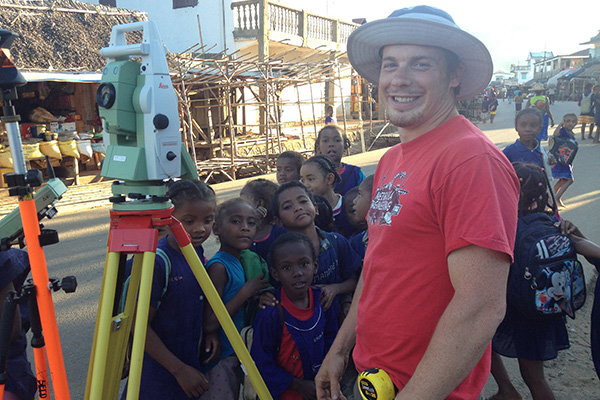 Nebraska Engineering Student surveying while on a mission with children standing in the background