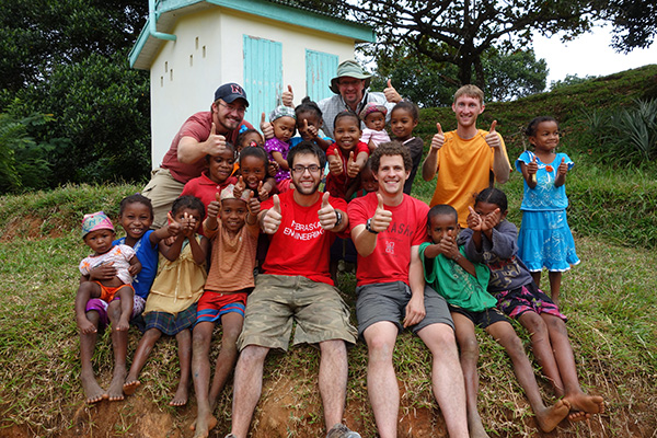 Nebraska Engineering Students and local children give a thumbs up on a mission trip