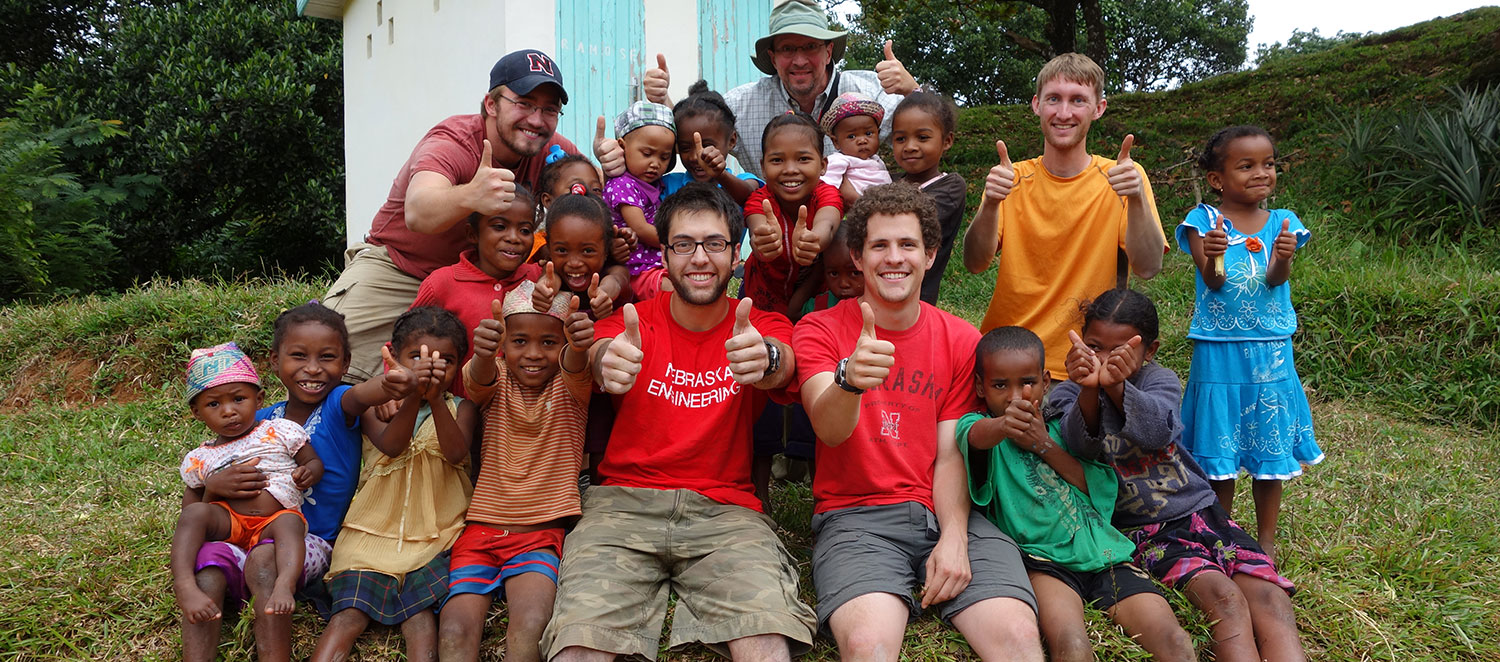 Nebraska Engineering Students sitting with local children giving a thumbs up during their mission trip