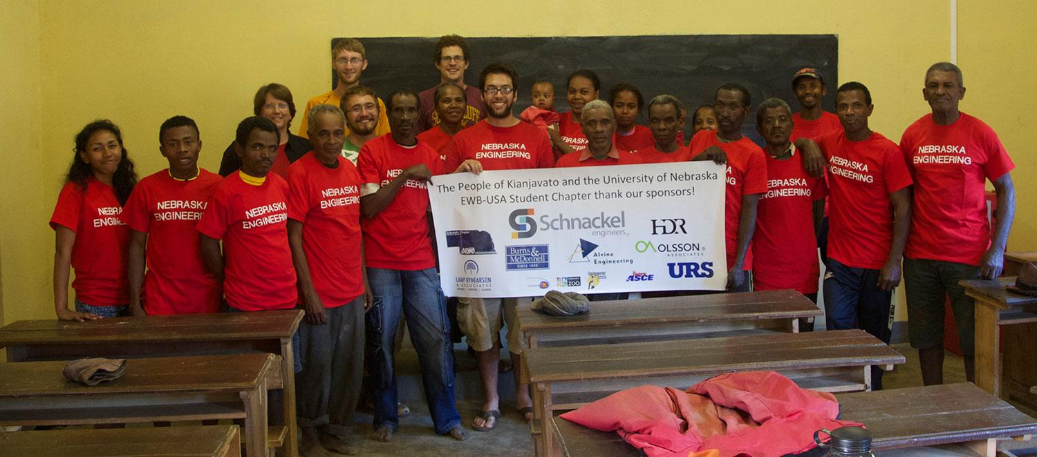 EWB Student Chapter standing with the people of Kianjavato with a sign displaying sponsors of their trip.